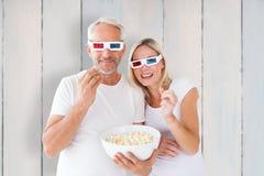 Immagine composita delle coppie felici che indossano i vetri 3d che mangiano popcorn Fotografie Stock