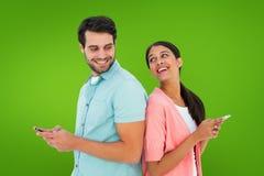 Immagine composita delle coppie felici che inviano i messaggi di testo Fotografie Stock Libere da Diritti