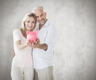 Immagine composita delle coppie felici che mostrano il loro porcellino salvadanaio Fotografia Stock