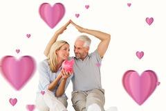 Immagine composita delle coppie felici che si siedono e che riparano porcellino salvadanaio Fotografia Stock Libera da Diritti