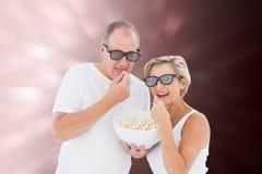Immagine composita delle coppie mature che indossano i vetri 3d che mangiano popcorn Fotografie Stock Libere da Diritti