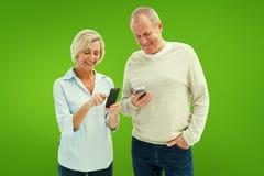 Immagine composita delle coppie mature felici facendo uso dei loro smartphones Fotografie Stock Libere da Diritti