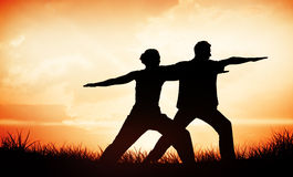 Immagine composita delle coppie pacifiche nell'yoga facente bianca insieme nella posizione del guerriero Fotografia Stock Libera da Diritti