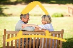 Immagine composita delle coppie pensionate felici che si siedono sul banco Immagini Stock Libere da Diritti