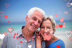 Immagine composita delle coppie senior nei cuori 3d dei biglietti di S. Valentino e della spiaggia Fotografia Stock