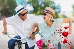 Immagine composita delle coppie senior sui cuori 3d dei biglietti di S. Valentino e della bici Fotografia Stock