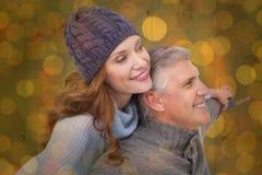 Immagine composita delle coppie spensierate in abbigliamento caldo Fotografie Stock Libere da Diritti