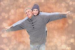 Immagine composita delle coppie spensierate in abbigliamento caldo Immagini Stock