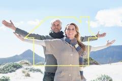 Immagine composita delle coppie spensierate che stanno sulla spiaggia in abbigliamento caldo Fotografia Stock