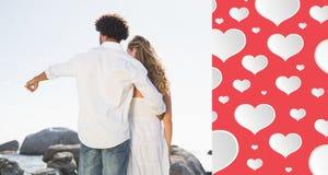 Immagine composita delle coppie splendide che guardano fuori al mare Fotografia Stock