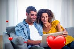 Immagine composita delle coppie sui cuori 3d dei biglietti di S. Valentino e del sofà Immagini Stock Libere da Diritti