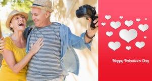 Immagine composita delle coppie turistiche felici che prendono un selfie nella città Fotografie Stock Libere da Diritti