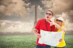 Immagine composita delle coppie turistiche felici facendo uso della mappa Immagini Stock Libere da Diritti