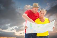 Immagine composita delle coppie turistiche perse facendo uso della mappa immagini stock libere da diritti