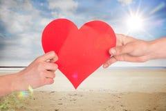 Immagine composita delle mani che tengono cuore rosso Fotografia Stock Libera da Diritti