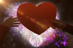 Immagine composita delle mani che tengono la carta arancio di forma del cuore Immagine Stock