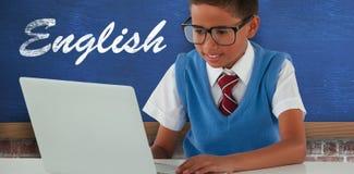 Immagine composita dello scolaro che per mezzo del computer portatile alla tavola Fotografie Stock