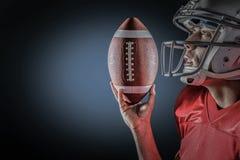 Immagine composita dello sportivo che cerca mentre tenendo football americano immagine stock libera da diritti