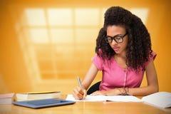 Immagine composita dello studente che si siede nella scrittura delle biblioteche Immagini Stock Libere da Diritti