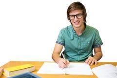 Immagine composita dello studente che si siede nella scrittura delle biblioteche Fotografie Stock Libere da Diritti