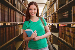 Immagine composita dello studente che sorride alla macchina fotografica in biblioteca Immagine Stock Libera da Diritti