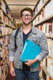 Immagine composita dello studente che sorride alla macchina fotografica in biblioteca Fotografia Stock