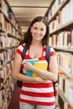 Immagine composita dello studente che sorride alla macchina fotografica in biblioteca Fotografie Stock Libere da Diritti