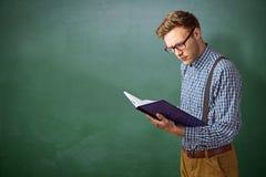 Immagine composita dello studente geeky che legge un libro Fotografia Stock Libera da Diritti