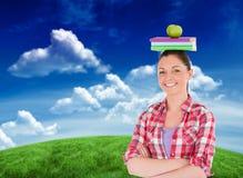 Immagine composita dello studente grazioso che tiene una mela ed i libri lei capa Fotografia Stock Libera da Diritti