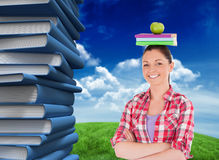 Immagine composita dello studente grazioso che tiene una mela ed i libri lei capa Fotografia Stock
