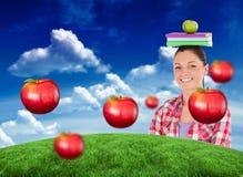 Immagine composita dello studente grazioso che tiene una mela ed i libri lei capa Immagine Stock