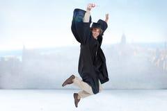 Immagine composita dello studente maschio felice nel salto laureato dell'abito Fotografia Stock