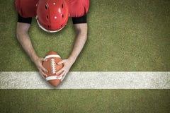 Immagine composita di calcio di raggiungimento del giocatore di football americano Fotografia Stock
