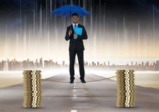 Immagine composita di Digital dell'uomo d'affari che tiene ombrello blu che equilibra sulla corda in mezzo della pila di monete Immagine Stock