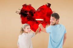 Immagine composita di giovane pittura delle coppie con il rullo Fotografia Stock Libera da Diritti
