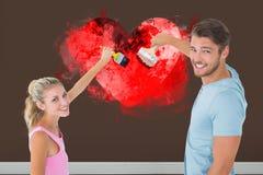 Immagine composita di giovane pittura delle coppie con le spazzole Immagini Stock