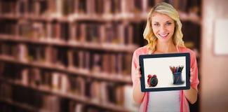 Immagine composita di giovane studente grazioso che mostra il pc della compressa Immagine Stock
