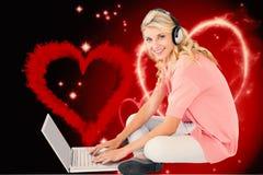 Immagine composita di giovane studente grazioso che per mezzo del computer portatile Fotografia Stock Libera da Diritti