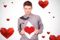 Immagine composita di giovane uomo attraente che tira alla sua maglietta immagini stock libere da diritti