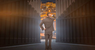 Immagine composita di giovane uomo d'affari che sta di nuovo alla macchina fotografica che graffia il suo 3d capo Fotografia Stock