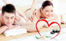 Immagine composita di giovani coppie attraenti che godono di un massaggio posteriore Fotografie Stock