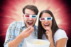Immagine composita di giovani coppie attraenti che guardano un film 3d Fotografia Stock