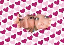 Immagine composita di giovani coppie che danno una occhiata attraverso la carta lacerata Immagine Stock