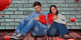 Immagine composita di giovani coppie che si siedono sul pavimento con cuore rotto 3D Immagini Stock Libere da Diritti