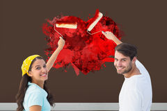 Immagine composita di giovani coppie felici che dipingono insieme Fotografia Stock Libera da Diritti