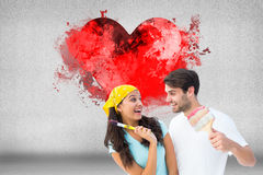 Immagine composita di giovani coppie felici che dipingono insieme e che ridono Immagine Stock