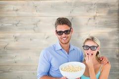 Immagine composita di giovani coppie felici che indossano i vetri 3d che mangiano popcorn Immagine Stock Libera da Diritti