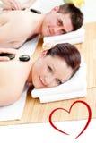 Immagine composita di giovani coppie sveglie che ricevono un massaggio posteriore con le pietre calde Immagini Stock