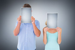 Immagine composita di giovani pagine della tenuta delle coppie sopra i loro fronti Fotografie Stock Libere da Diritti