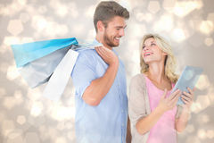 Immagine composita di giovani sacchetti della spesa attraenti della tenuta delle coppie che esaminano il pc della compressa Fotografia Stock